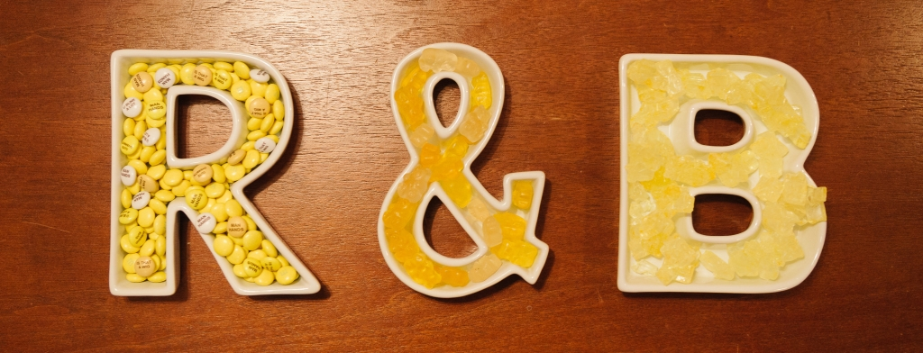 A photograph of R & B made of white porcelain candy dishes, filled with yellow candies.